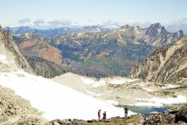 Senderistas admirando montañas en un paisaje remoto, Leavenworth, Washington, EE.UU. - foto de stock