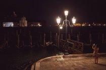 Turista donna che fotografa il lampione in laguna a Venezia, Veneto, Italia di notte . — Foto stock