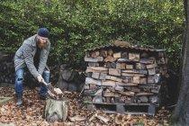 Бородатый мужчина в черной шапочке и парке, стоящий в саду осенью, используя топор, чтобы рубить кусок дерева на рубке . — стоковое фото