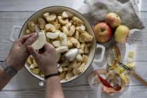 Close-up of woman placing apples in round baking tin. — Stock Photo