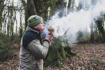 Человек, стоящий в лесу и дующий на пучок соломы воспламеняющийся огонь . — стоковое фото