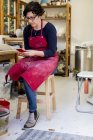 Mulher de avental vermelho sentado nas fezes na oficina de cerâmica e verificando o telefone móvel . — Fotografia de Stock