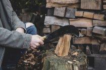 Крупный план человека с помощью мачете тесак на рубке блока, расщепление кусок дерева . — стоковое фото