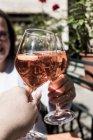 Женщина, сидящая за столом и тост с бокалами вина алкогольного напитка с мужчиной . — стоковое фото