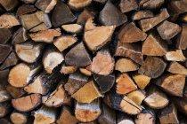 Cadre complet de bûches de bois empilées rustiques . — Photo de stock