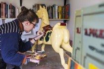 Frau steht in Werkstatt und bemalt traditionelles hölzernes Karussell-Pferd aus Karussell. — Stockfoto