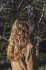 Vista posteriore di ragazza adolescente con lunghi capelli castani ondulati in piedi all'aperto — Foto stock