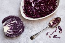 Dish and spoon of sliced red cabbage and half of raw cabbage. - foto de stock