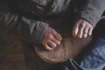 Высокоугольный крупный план человека, сидящего в мастерской, держа кусок дерева . — стоковое фото