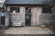 Бородатый мужчина стоит в дверях деревянной мастерской, держит синюю кружку и смотрит в камеру . — стоковое фото