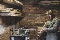 Бородатый мужчина стоит в мастерской, носит защитные ушки, работает на куске дерева . — стоковое фото