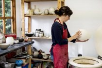 Woman in red apron standing in workshop next to kiln and holding ceramic vase. — Stock Photo