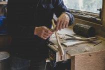 Человек, стоящий на рабочем месте в мастерской, работающий над куском дерева . — стоковое фото