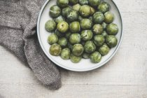 High angle close-up of fresh greengages in white bowl. — стокове фото