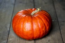 Close-up of bright orange pumpkin on rustic wooden table. — Stock Photo