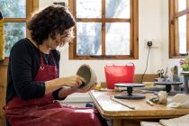 Woman in red apron sitting in ceramics workshop and working on small clay bowl. — Stock Photo