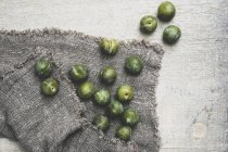 High angle close-up of fresh greengages on grey cloth. — Stock Photo