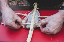 High angle close up of person preparing fish on wooden skewer for grilling. — Stock Photo