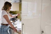 Mulher em pé na cozinha doméstica e cera de vela agitação . — Fotografia de Stock