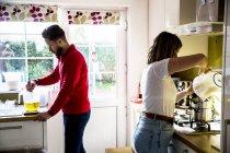 Mann und Frau stehen in der heimischen Küche und stellen Glaskerzen her. — Stockfoto