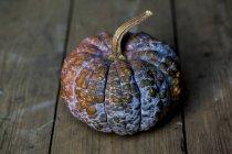 Nahaufnahme von lila und orangefarbenem Kürbis auf rustikalem Holztisch. — Stockfoto