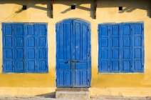 Blue doors and windows in building facade — Stock Photo