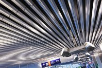 Lighting and signs on corrugated style ceiling in airport — Stock Photo