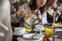 Mid adult women sitting at table, pouring tea from silver tea pot. — Stock Photo