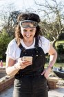 Smiling woman wearing dungarees and protective goggles checking mobile phone. — Stock Photo