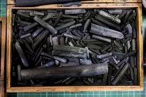 Високий кут крупним планом дерев'яної коробки з виділенням деревного вугілля в різних розмірах. — стокове фото