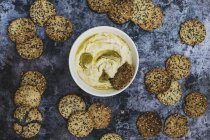 Top view of bowl of hummus and freshly baked seeded crackers. — Stock Photo