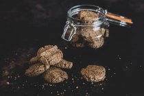 Primo piano ad alto angolo di biscotti al cioccolato appena sfornati in barattolo di vetro e superficie nera . — Foto stock