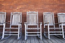 Row of wooden rocking chairs against brick wall — Stock Photo