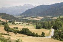 Vallée avec des champs et des fermes et des montagnes à distance, France — Photo de stock