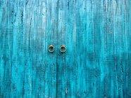 Old blue wooden doors with round doorknobs — Stock Photo