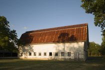 Bâtiment de ferme avec le toit rouillé rouge et les murs de bardeaux et la rangée des fenêtres bas dans le mur. — Photo de stock