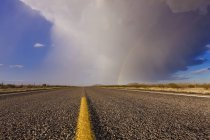 Storm and rainbow along highway road in desert — Stock Photo