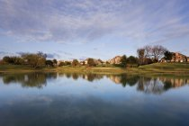 Houses reflecting in pond water in village — Stock Photo