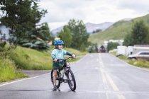 Elementary age boy straddling bike on rainy road. — Stock Photo