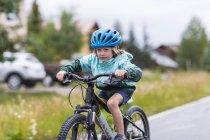 Старшеклассник на велосипеде по дождливой дороге . — стоковое фото