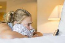 Девочка-подросток лежит на кровати в номере отеля и смотрит на смартфон . — стоковое фото