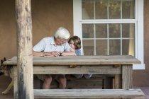 Старший дідусь розмовляє з маленьким онуком у сільському дворі.. — стокове фото