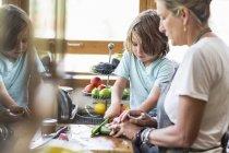 Mãe e filho pequeno cortando legumes e fazendo salada na cozinha . — Fotografia de Stock