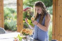 Blondes Teenager-Mädchen arrangiert Rosen aus dem Garten. — Stockfoto