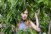 Blonde teenage girl standing among green branches of tree. — Stock Photo