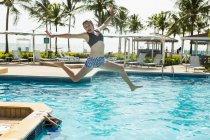 Blonde adolescente bondissant dans la piscine . — Photo de stock