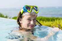 Blonde teenage girl in goggles swimming in infinity pool. — Stock Photo