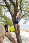 Madre fotografiando juguetona hija adolescente en el árbol en la playa . - foto de stock