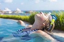 Rubia adolescente chica relajarse en piscina infinita. - foto de stock