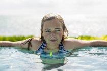 Blonde teenage girl swimming in infinity pool. — Stock Photo